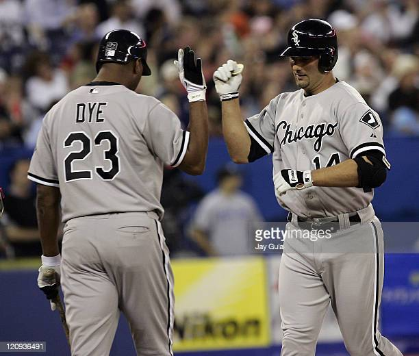 Paul Konerko is congratulated by Jermaine Dye after slugging a solo HR for the Chicago White Sox against the Toronto Blue Jays at Rogers Centre in...