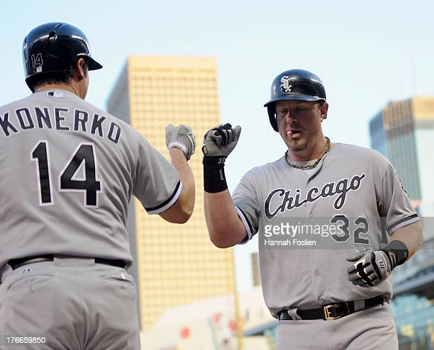 Paul Konerko of the Chicago White Sox congratulates teammate Aaron Hicks on hitting a solo home run against the Minnesota Twins during the third...