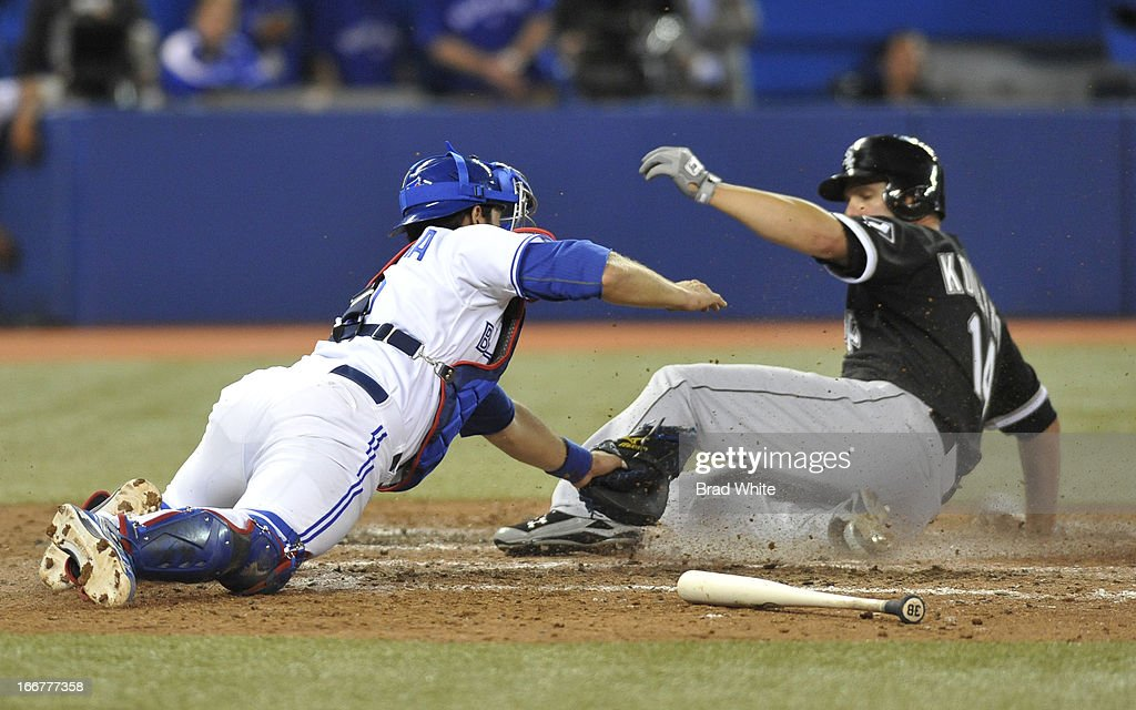 Paul Konerko #14 of the Chicago White Sox scores the winning run in the ninth inning ahead of the tag of catcher J.P. Arencibia #9 of the Toronto Blue Jays during MLB-game action April 16, 2013 at Rogers Centre in Toronto, Ontario, Canada.
