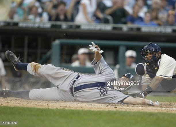 Paul Konerko of the Chicago White Sox slides over home plate as he is tagged by catcher Ivan Rodriguez of the Detroit Tigers during the game on July...