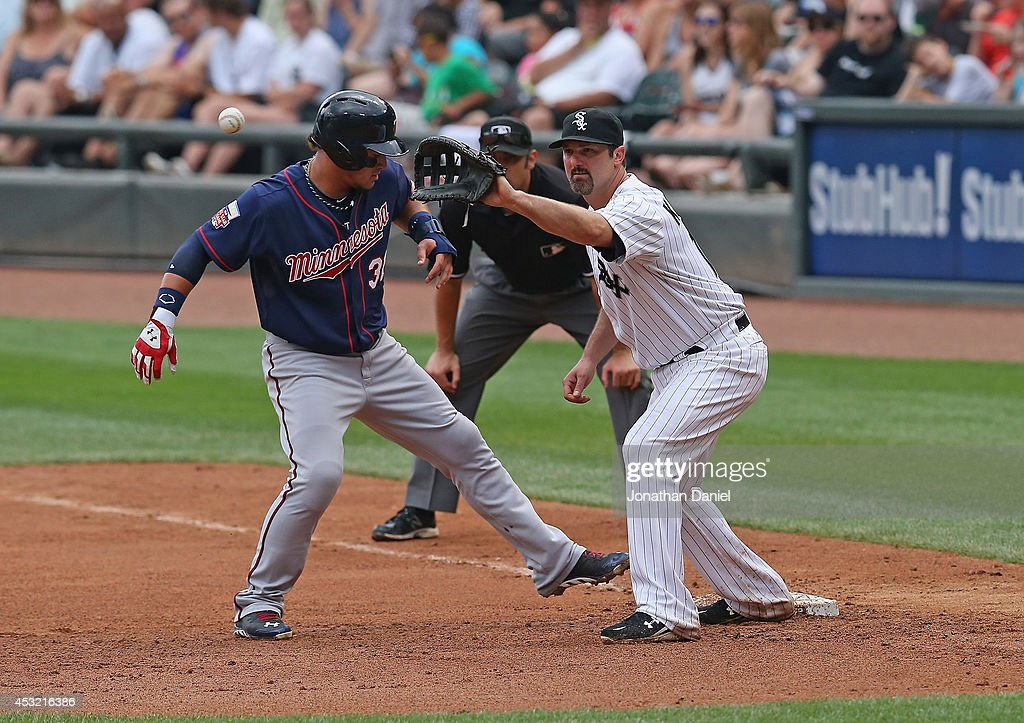 Paul Konerko #14 of the Chicago White Sox takes a throw as Oswaldo Arcia #31 of the Minnesota Twins moves back to first base at U.S. Cellular Field on August 3, 2014 in Chicago, Illinois. The Twins defeated the White Sox 16-3.