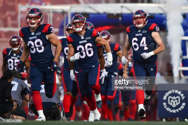 Paul Kozachuk and teammate Sean Jamieson of the Montreal Alouettes take to the field against the Hamilton TigerCats during the CFL game at Percival...