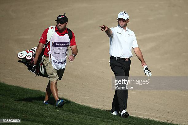 Paul Lawrie of Scotland consults with caddy Davy Kenny on the fourteenth hole during the first round of the Omega Dubai Desert Classic at The...