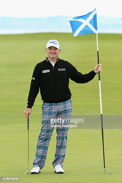 Paul Lawrie of Scotland holds the flag on the ninth green during the ProAm prior to the start of the Aberdeen Asset Management Scottish Open at...