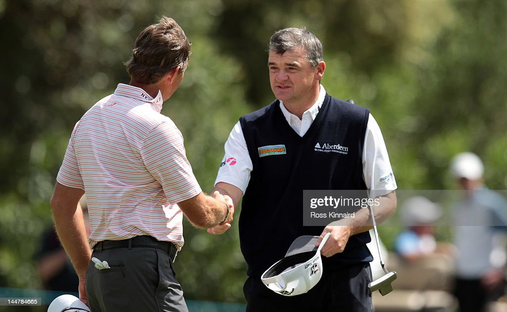 Paul Lawrie of Scotland is congratulated by Retief Goosen of South Africa after the quarter final matches on day three of the Volvo World Match Play Championship at Finca Cortesin Golf Club on May 19, 2012 in Casares, Spain.