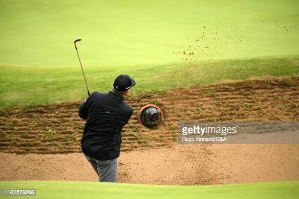 Paul Lawrie of Scotland plays a bunker shot on the 13th hole with a TV camera mounted in the bunker during a practice round prior to the 148th Open...