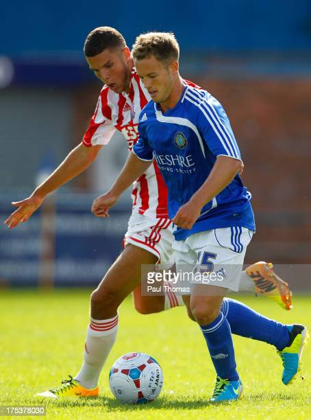 Paul Lewis of Macclesfield in action with Karim Rossi of Stoke City during the Pre Season Friendly match between Macclesfield Town and Stoke City at...