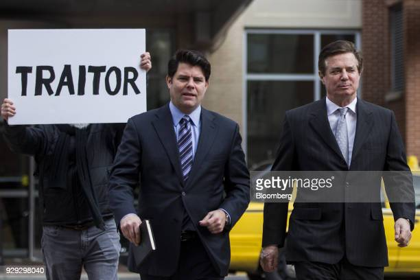 Paul Manafort former campaign manager for Donald Trump right arrives as a man holds a sign reading 'Traitor' outside the District Courthouse in...