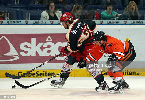 Paul Manning of Hannover and Sebastian Furchner of Wolfsburg battle for the puck during the DEL match between Hannover Scorpions and Grizzly Adams...