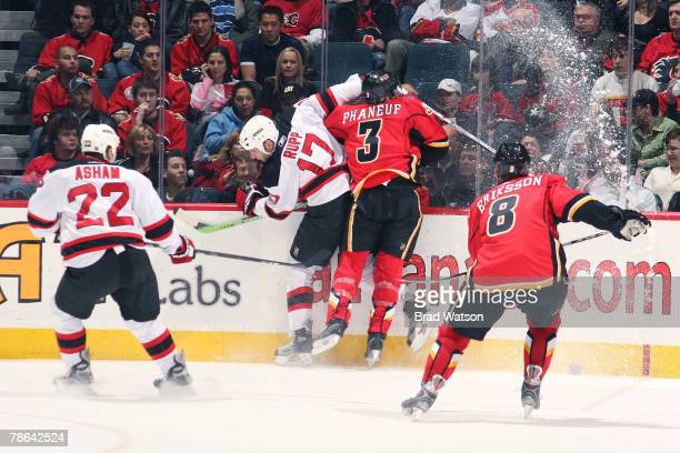 Paul Martin of the Calgary Flames checks Michael Rupp of the New Jersey Devils on December 23, 2007 at Pengrowth Saddledome in Calgary, Alberta,...