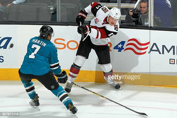 Paul Martin of the San Jose Sharks attempts to block a shot from Lawson Crouse of the Arizona Coyotes during a NHL game at SAP Center at San Jose on...