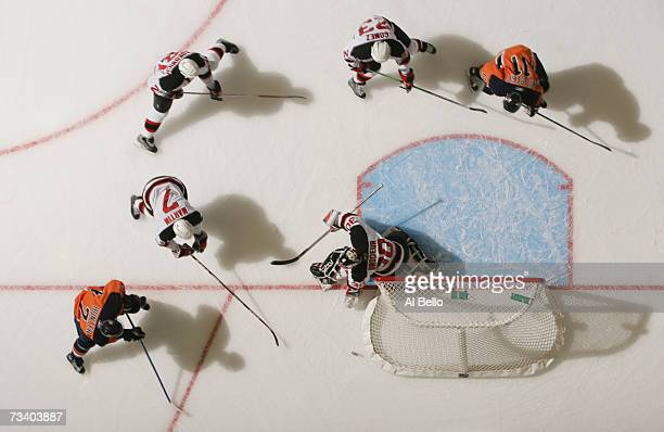 Paul Martin Scott Gomez and Brad Lukowich of the New Jersey Devils help defend as Trent Hunter of the New York Islanders tries to get the puck past...