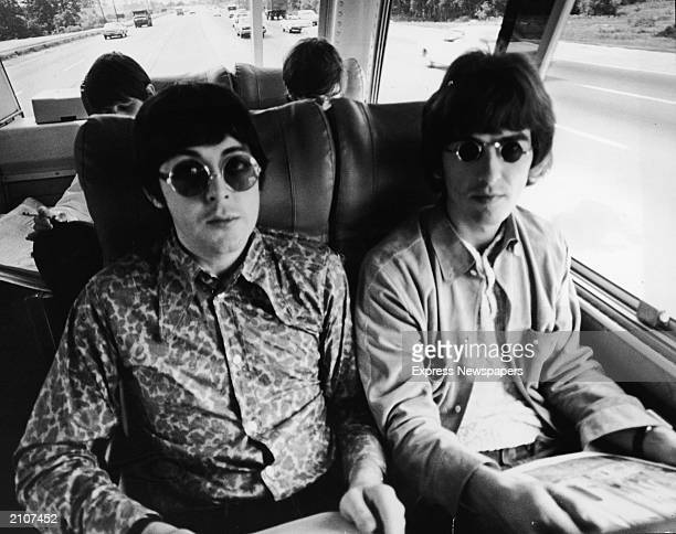 Paul McCartney and George Harrison sit next to each other on their tour bus during a Beatles American tour c 1966 Behind them sit Ringo Starr and...