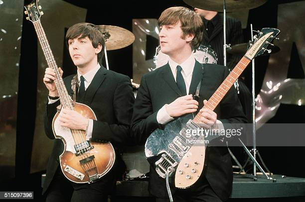 Paul McCartney and John Lennon hold their guitars while on the set of The Ed Sullivan Show at the CBS television studios in Manhattan, where the Fab...