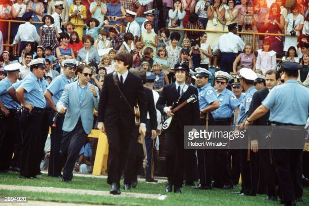 Paul McCartney and John Lennon of the Beatles walk out at Comiskey Park Chicago 20th August 1965
