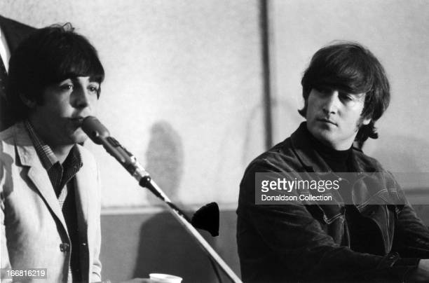 Paul McCartney and John Lennon of the rock and roll group 'The Beatles' at a press conference for the release of their album 'Help' at the Capitol...
