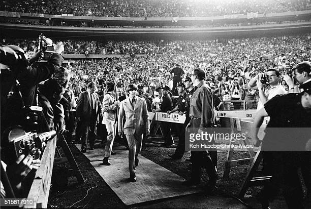 Paul McCartney and Ringo Starr of The Beatles walk through the crowds towards the stage before a show at Shea Stadium New York August 23 1966