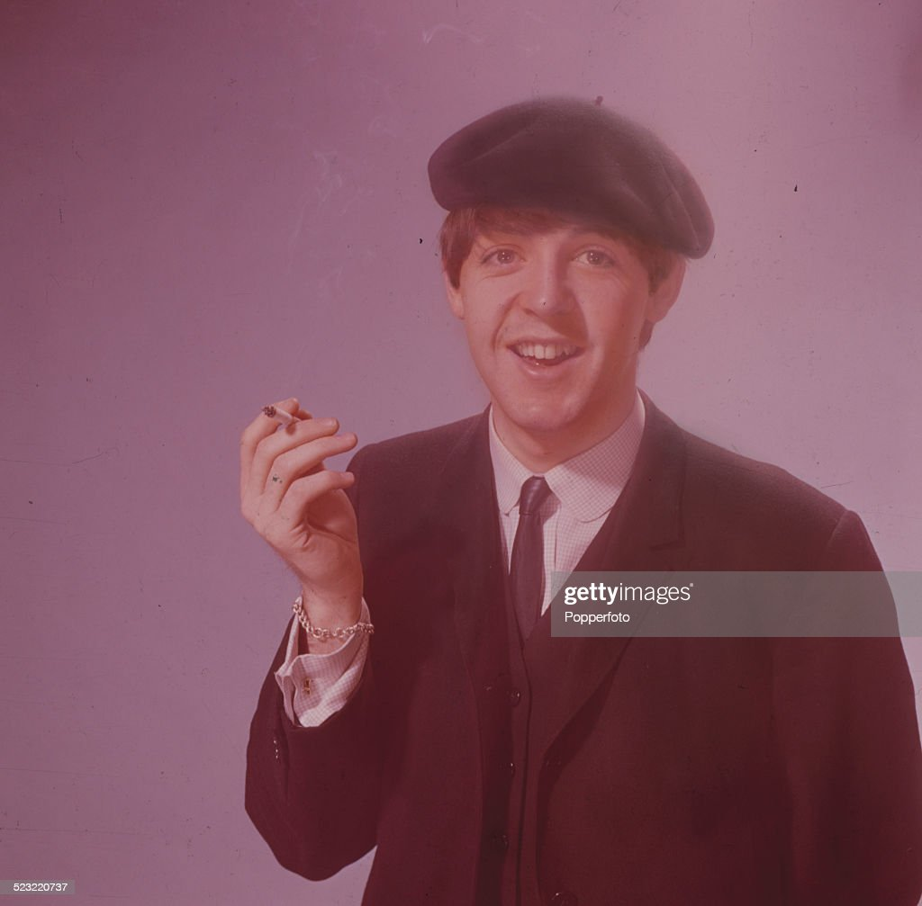 Paul McCartney, bassist with the Beatles pictured wearing a beret and smoking a cigarette in a photographic studio in Paris in January 1964.