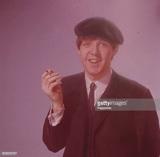 Paul McCartney bassist with the Beatles pictured wearing a beret and smoking a cigarette in a photographic studio in Paris in January 1964