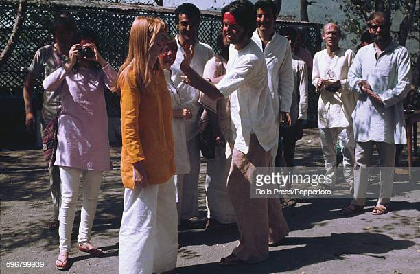 Paul McCartney from The Beatles pictured daubing red paint on the face of his girlfriend Jane Asher during a 'holi' ceremony observed by various...