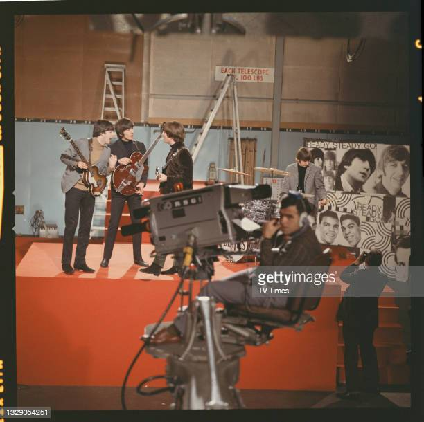 Paul McCartney, George Harrison, John Lennon and Ringo Starr of English rock and roll group The Beatles rehearsing before an appearance on music...