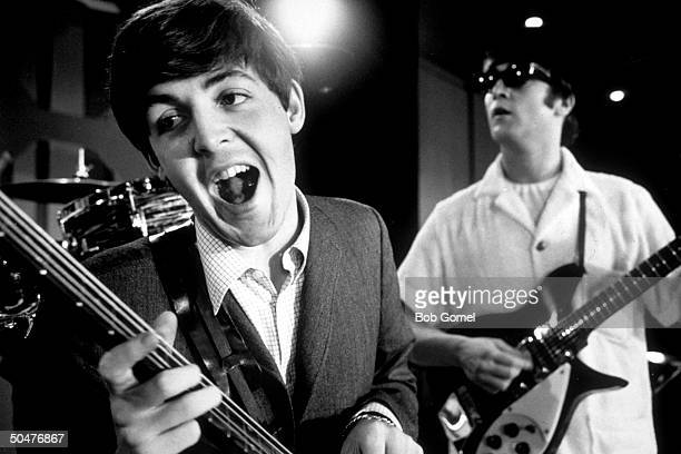 Paul McCartney John Lennon of rock group the Beatles rehearsing on stage during American tour