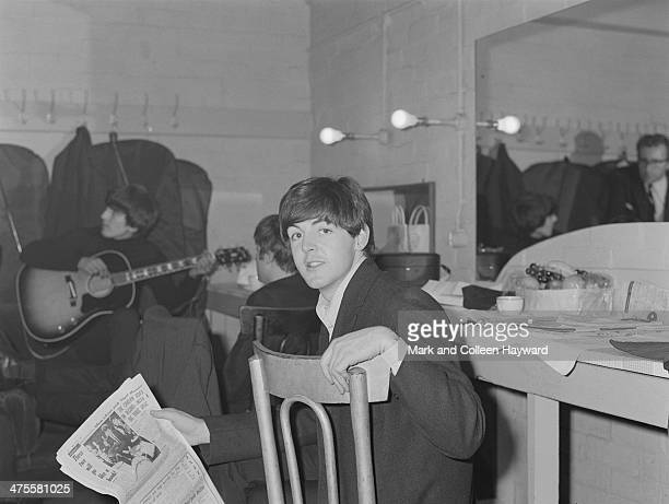 Paul McCartney of The Beatles holding a copy of Disc magazine in a dressing room at the Gaumont Cinema Doncaster 10th December 1963 Behind him are...