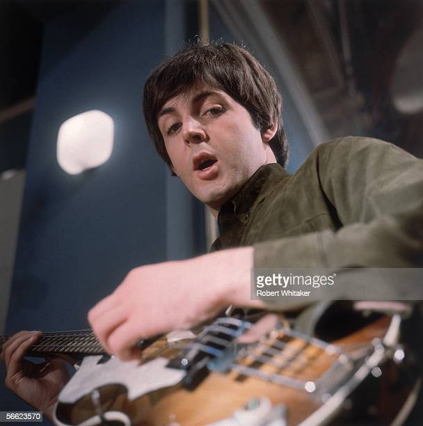 Paul McCartney of the Beatles singing and playing guitar during a recording session at Abbey Road