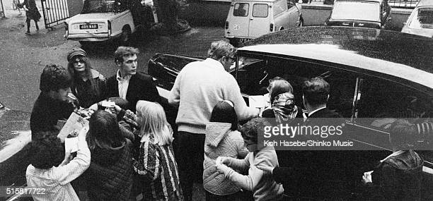 Paul McCartney of The Beatles sings autographs for a crowd of fans outisde EMI Studios Abbey Road London June 15 1965 Neil Aspinall and Mal Evans are...