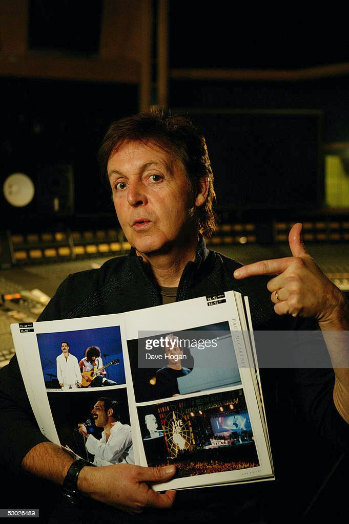 Paul McCartney points to a picture of himself in a souvenir photo book of the 1985 Live Aid charity concert, Air Studios, London 24th November 2004. Twenty years after its release, the original charity single, 'Do They Know It's Christmas', is being re-recorded and released under the name Band Aid 20 with MacCartney on bass guitar.