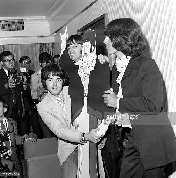 LR Paul McCartney Ringo Starr and George Harrison with a cutout cartoon of John Lenon July 1968 Y06939