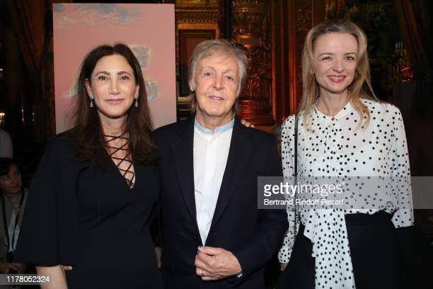 Paul McCartney standing between his wife Nancy Shevell and Louis Vuitton's executive vice president Delphine Arnault attend the Stella McCartney...