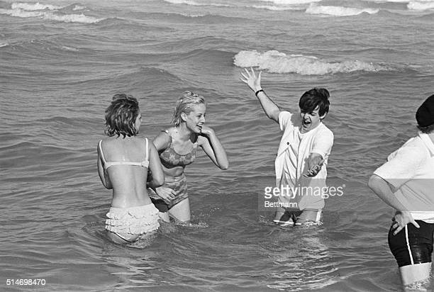 Paul McCartney taking advantage of some relaxation time on the Beatles' 1964 concert tour splashes in the Atlantic at Miami Beach with two girls