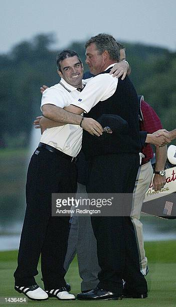 Paul McGinley and Darren Clarke of Europe celebrate on the 18th green after halfing their match during the afternoon fourball matches on the second...