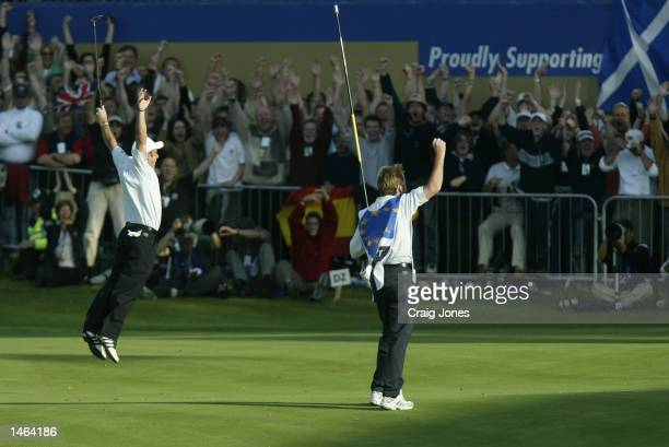 Paul McGinley of Europe celebrates after holing his par putt on the 18th green to halve his match against Jim Furyk in the final day singles and...
