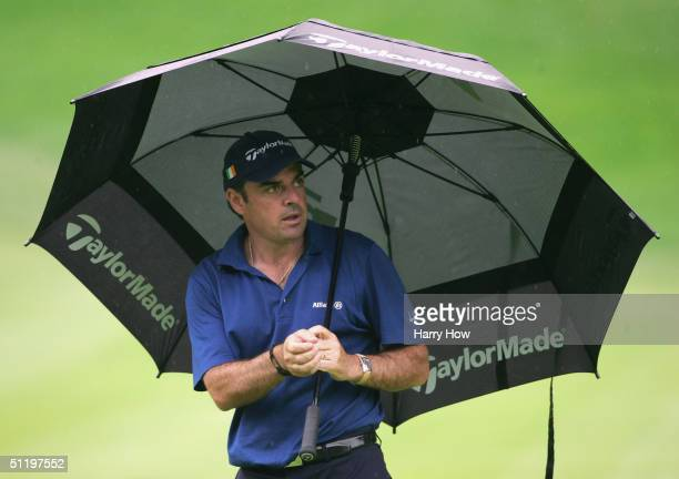 Paul McGinley of Irleland waits under his umbrella on the 18th hole during the second round of the NEC Invitational at the Firestone Country Club on...