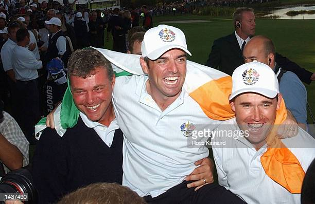 Paul McGinley Padraig Harrington and Darren Clarke of Ireland celebrate on the 18th green after Europe win the Ryder Cup during the singles matches...
