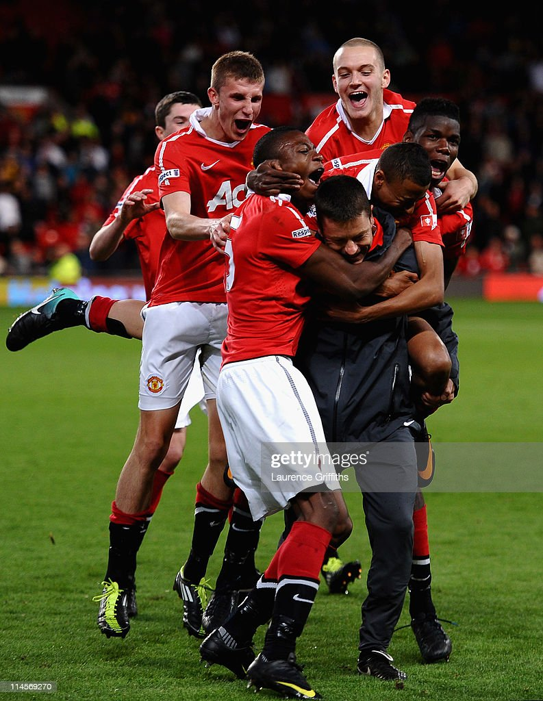 Paul McGuinness of Manchester United is mobbed by his players after victory in the FA Youth Cup Final 2nd Leg match between Manchester United and Sheffield United at Old Trafford on May 23, 2011 in Manchester, England.