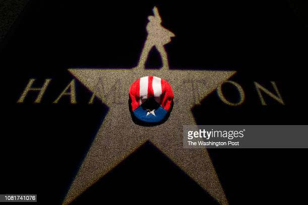 Paul McQue a Hamilton fan puts his Puerto Rico flag hat over a logo projection at the premiere of the awardwinning Broadway musical Hamilton in...