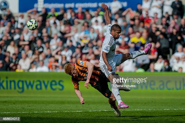 Paul McShane of Hull City and Wayne Routledge of Swansea City clash during the Barclays Premier League match between Swansea City and Hull City at...