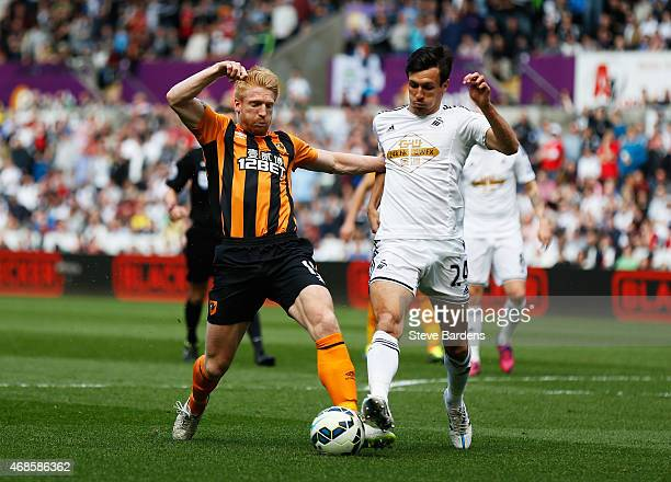 Paul McShane of Hull City is challenged by Jack Cork of Swansea City during the Barclays Premier League match between Swansea City and Hull City at...
