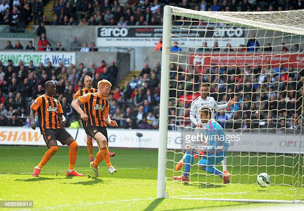 Paul McShane of Hull City scores past Lukasz Fabianski of Swansea City during the Barclays Premier League match between Swansea City and Hull City at...