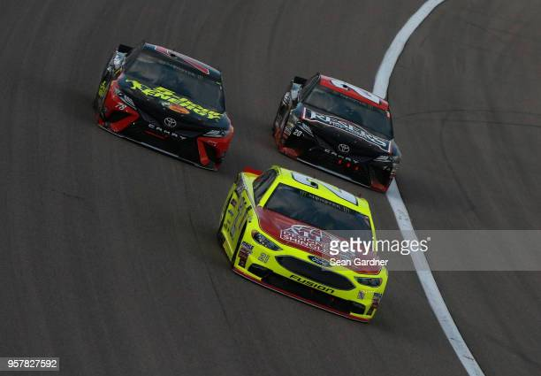 Paul Menard driver of the Menards/Atlas Ford leads Martin Truex Jr driver of the 5hour ENERGY/Bass Pro Shops Toyota and Erik Jones driver of the...