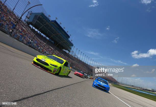 Paul Menard driver of the Menards/Sylvania Ford and Ryan Blaney driver of the PPG Ford lead the field prior to the start of the Monster Energy NASCAR...