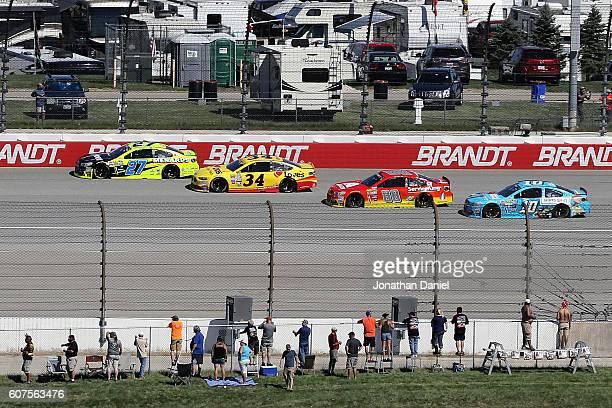 Paul Menard driver of the Moen/Menards Chevrolet leads Chris Buescher driver of the Love's Travel Stops Ford Alex Bowman driver of the Axalta...