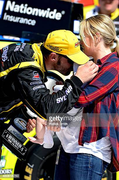 Paul Menard, driver of the Nibco/Menards Chevrolet, left, celebrates in victory lane with wife Jennifer and daughter Remi after winning the NASCAR...