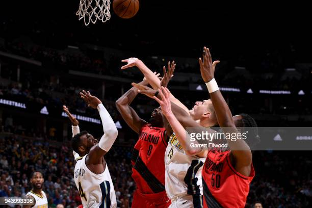 Paul Millsap and Nikola Jokic of the Denver Nuggets and AlFarouq Aminu and Caleb Swanigan of the Portland Trail Blazers jump for the rebound on APRIL...