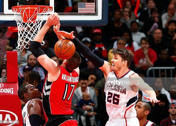 Paul Millsap defends as Kyle Korver of the Atlanta Hawks blocks a shot by Jonas Valanciunas of the Toronto Raptors at Philips Arena on February 20,...