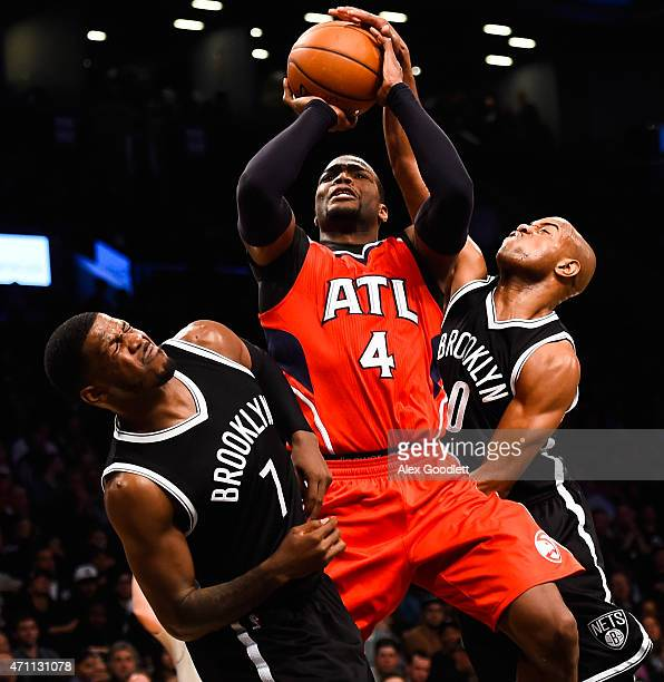 Paul Millsap of the Atlanta Hawks attempts a shot over Jarrett Jack and Joe Johnson of the Brooklyn Nets during the first round of the 2015 NBA...