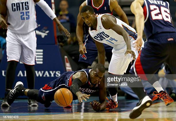 Paul Millsap of the Atlanta Hawks dives after a loose ball with Michael KiddGilchrist of the Charlotte Bobcats during their game at Time Warner Cable...